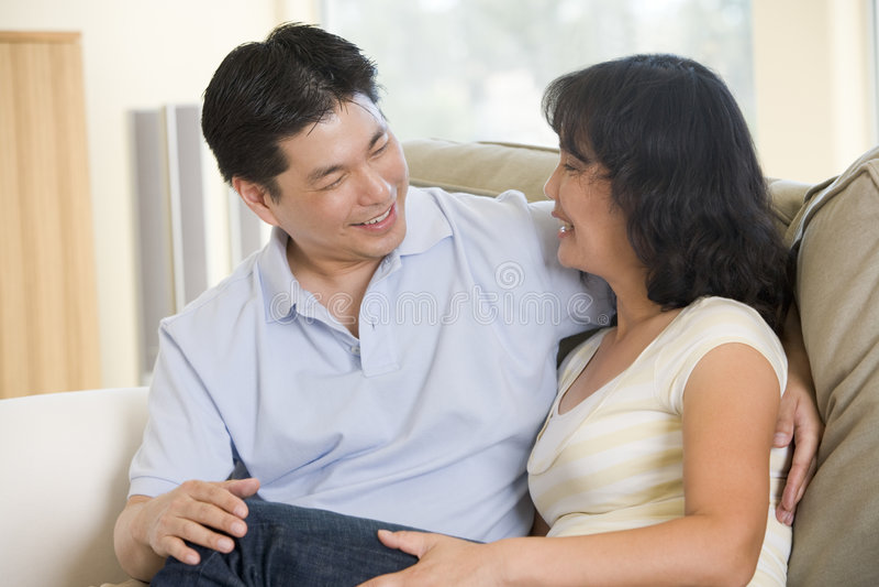 Het ontspannen van het paar in en woonkamer die spreekt glimlacht royalty-vrije stock fotografie