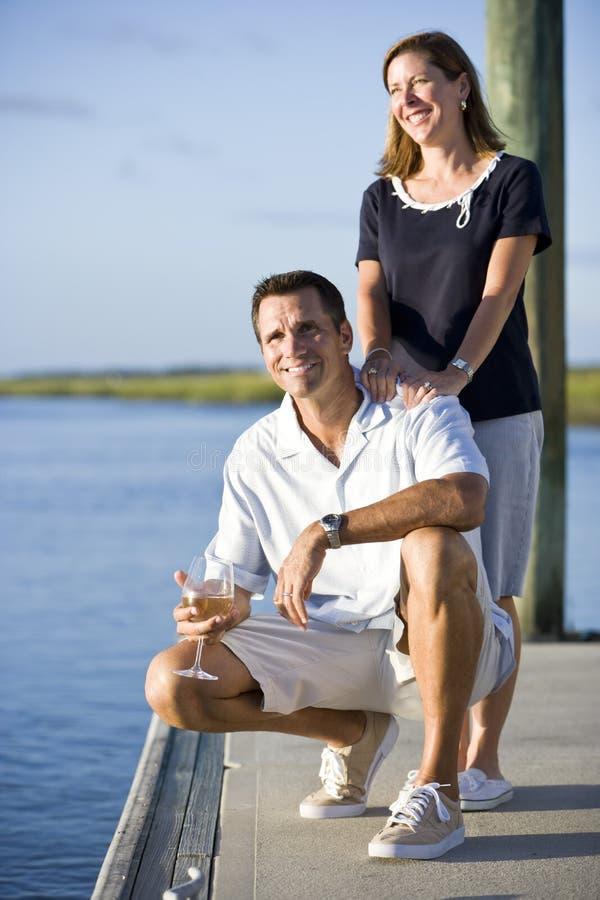 Het ontspannen van het paar met drank op dok door water royalty-vrije stock fotografie