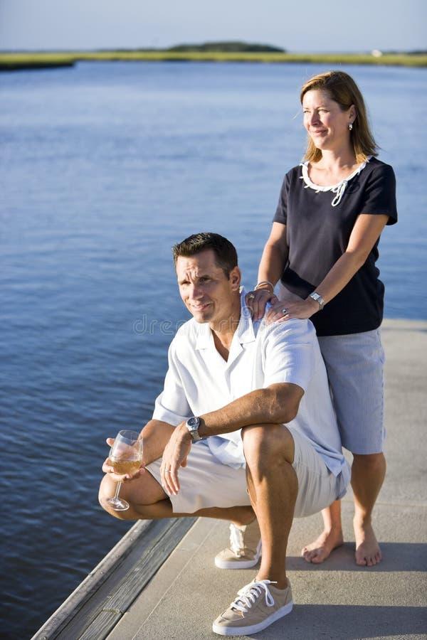 Het ontspannen van het paar met drank op dok door water royalty-vrije stock foto's