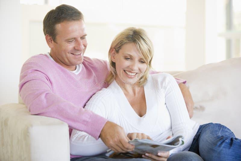 Het ontspannen van het paar met een tijdschrift en het glimlachen royalty-vrije stock foto's