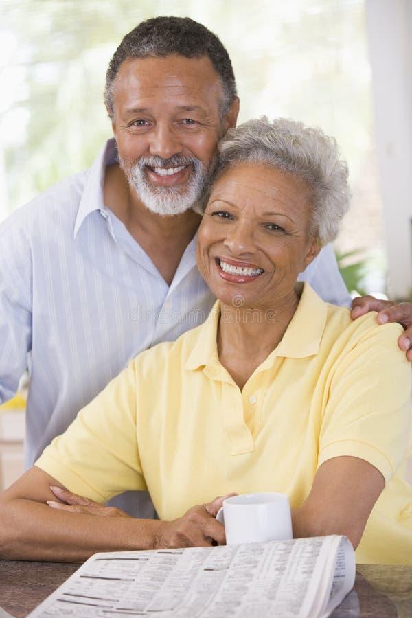 Het ontspannen van het paar met krant het glimlachen