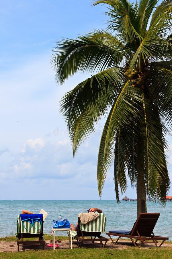 Het ontspannen van het paar op het strand van een tropisch eiland royalty-vrije stock fotografie