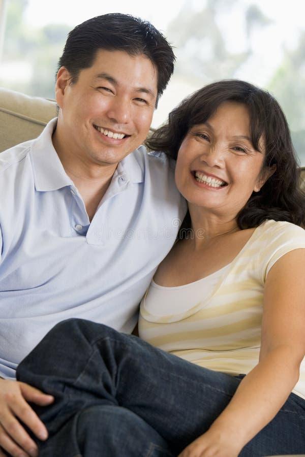 Het ontspannen van het paar in woonkamer en het glimlachen stock foto