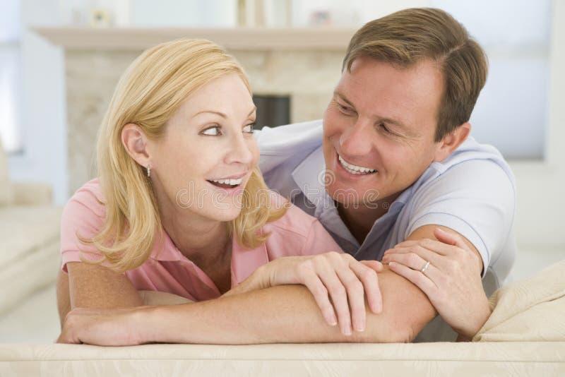 Het ontspannen van het paar in woonkamer en het glimlachen royalty-vrije stock afbeelding