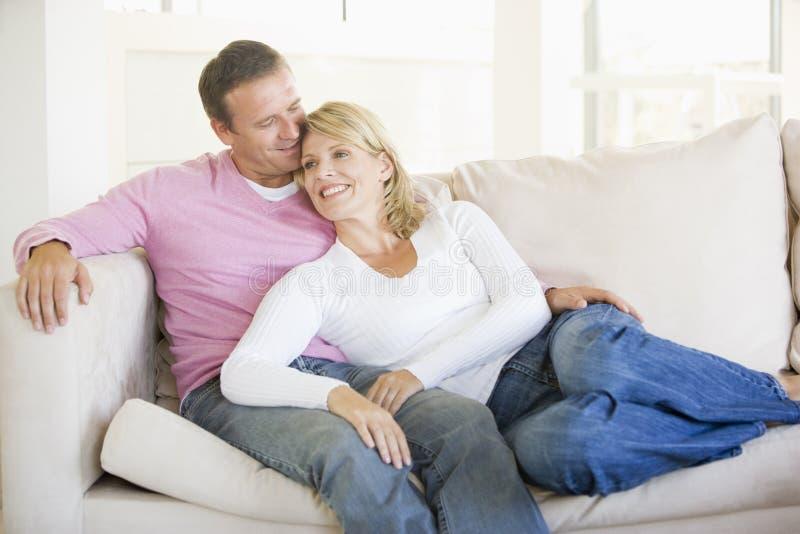 Het ontspannen van het paar in woonkamer en het glimlachen