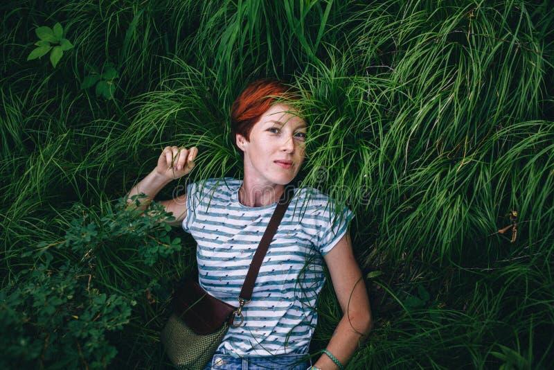 Het ontspannende roodharige hipster meisje ligt in het groene gras royalty-vrije stock fotografie