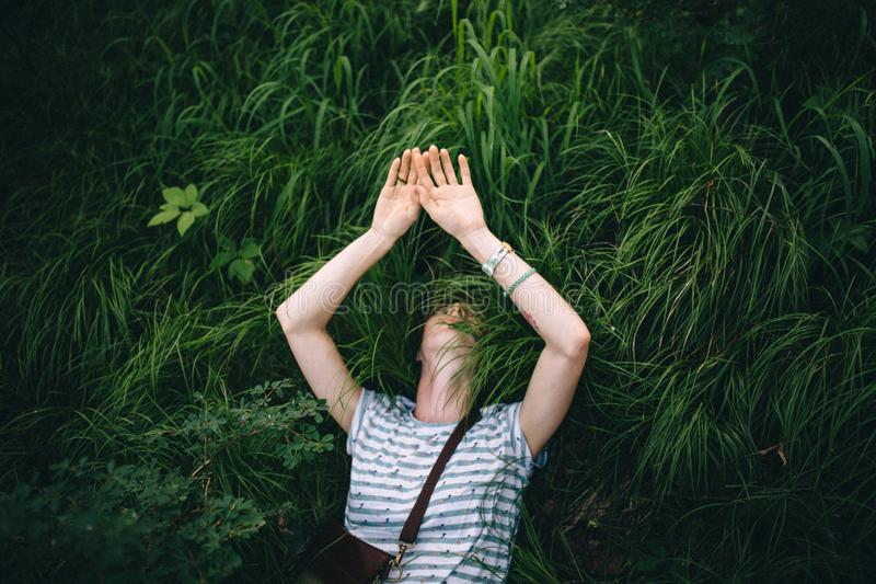 Het ontspannende roodharige hipster meisje ligt in het groene gras stock foto