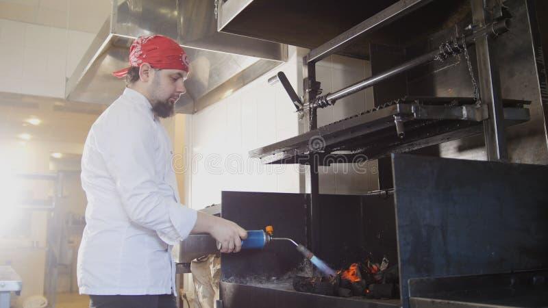 Het ontsteken van houtskool in de barbecueoven die een gasfornuis met behulp van stock afbeeldingen