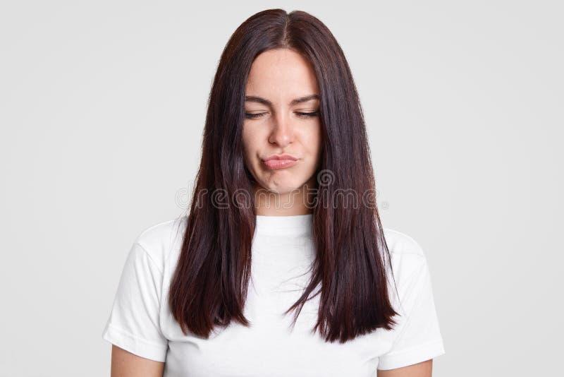 Het ontstemde donkerbruine jonge meisje pruilt lippen, heeft ontevredenheidsgelaatsuitdrukking, hoort negatieve commentaren over  royalty-vrije stock afbeeldingen