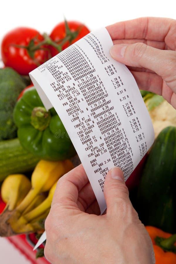 Het ontvangstbewijs van de kruidenierswinkel over een zak van groenten stock fotografie