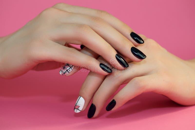 Het ontwerp van de spijkerskunst Handen met roze Manicure op roze Achtergrond royalty-vrije stock foto's