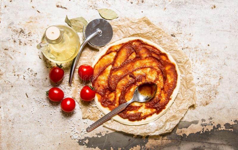 Het ontwikkelde pizzadeeg met tomaten, tomatenpuree en olijfolie royalty-vrije stock foto's