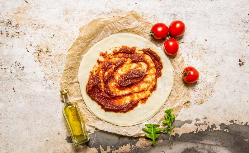 Het ontwikkelde pizzadeeg met tomatenpuree, olijfolie en tomaten stock afbeelding