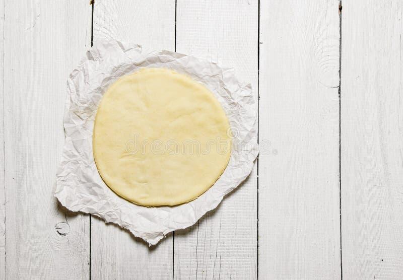 Het ontwikkelde pizzadeeg op het document stock fotografie