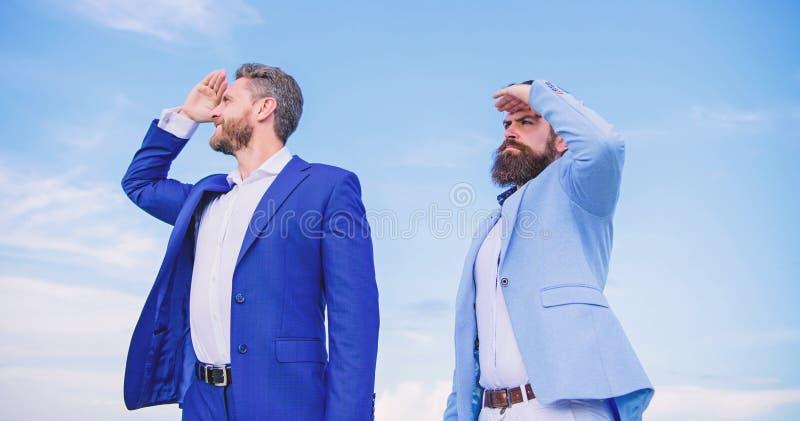 Het ontwikkelen van bedrijfsrichting Gaan de zakenlieden gebaarde gezichten achteruit om hemelachtergrond te steunen Managers van stock afbeeldingen