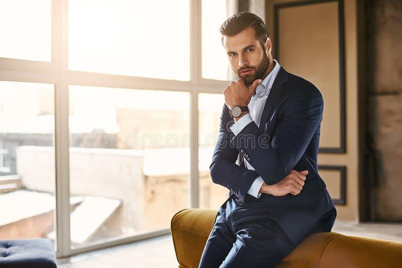 Het ontwikkelen van een nieuw idee De knappe en succesvolle zakenman in modieus kostuum denkt over iets terwijl status stock foto