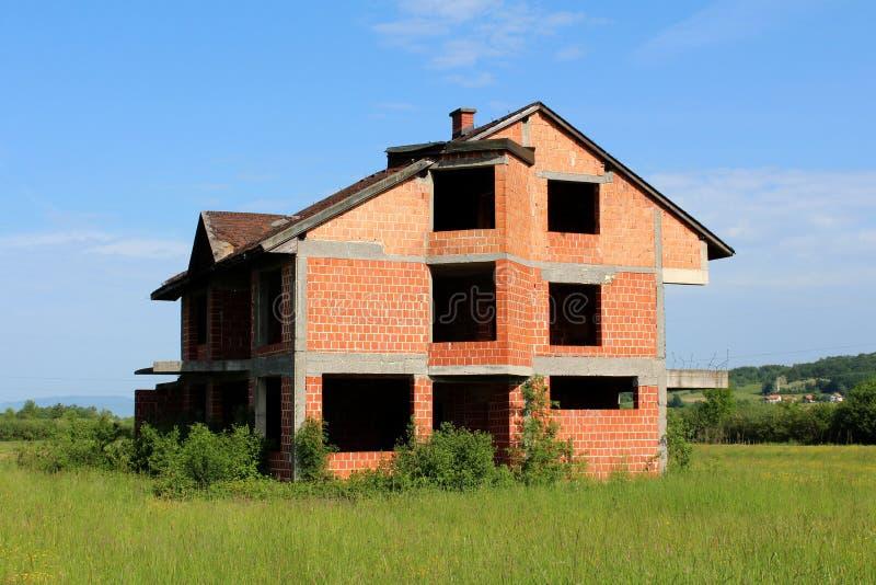 Het onvolledige huis in de voorsteden van de baksteenfamilie zonder deuren of vensters stock fotografie