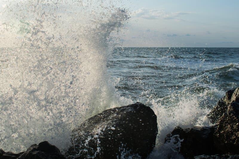 Het onweer begint op zee de golven raken de rotsen en het water is verspreid een hemel met zwarte wolken wordt behandeld die stock fotografie