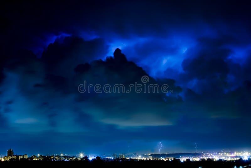 Het onweer van de bliksem over de stad stock afbeeldingen