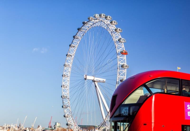 Het Oog van Londen en de iconische rode bus stock foto