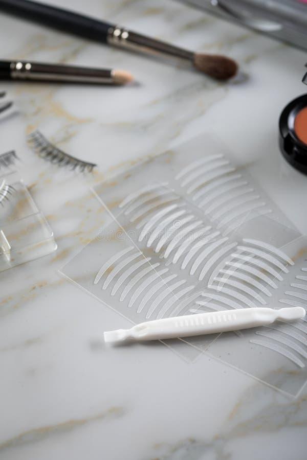 Het oogschaduwpalet, de borstels, de valse zwepen, het pincet en het kunstmatige ooglid vouwen dubbele banden voor oogmake-up op  royalty-vrije stock afbeeldingen