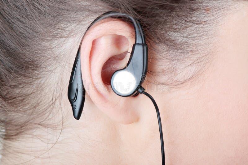 Het oor van de vrouw met hoofdtelefoons royalty-vrije stock foto's