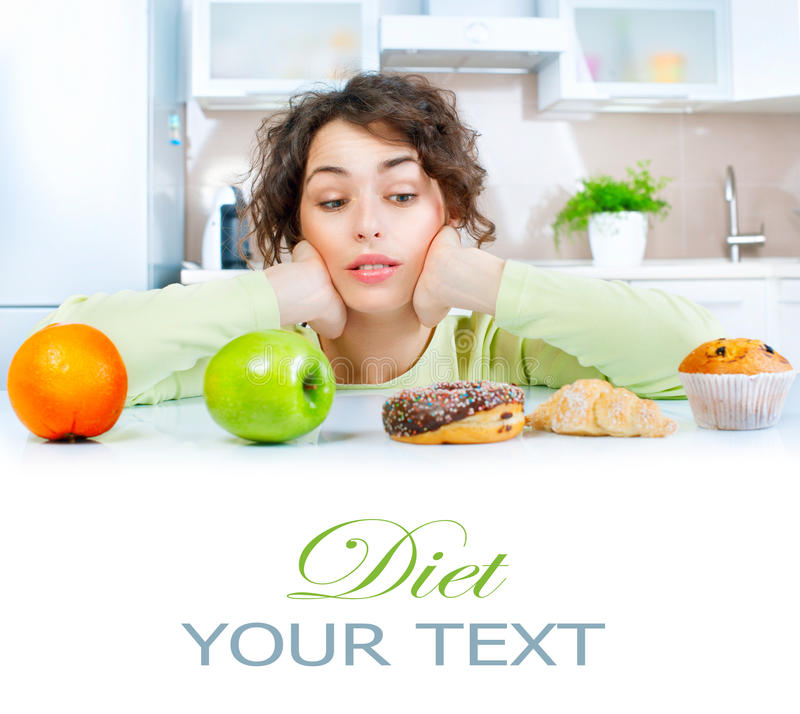 Het op dieet zijn concept Jonge vrouw die tussen vruchten en snoepjes kiezen stock foto's