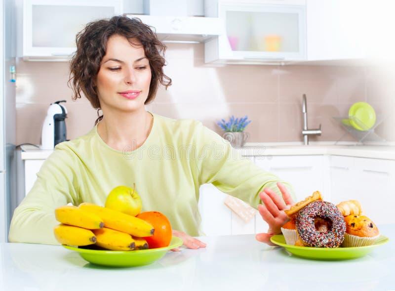 Het op dieet zijn concept Jonge vrouw die tussen vruchten en snoepjes kiezen stock afbeeldingen
