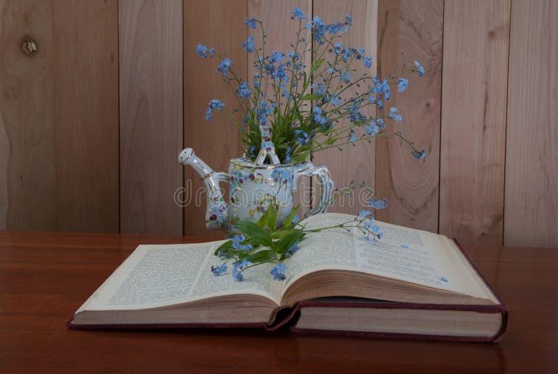 Het open boek met vergeet me niet bloemen stock afbeelding