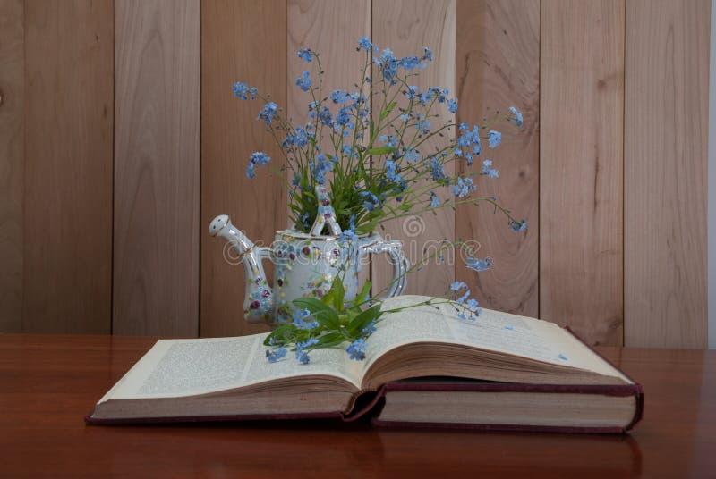Het open boek met vergeet me niet bloemen stock afbeeldingen