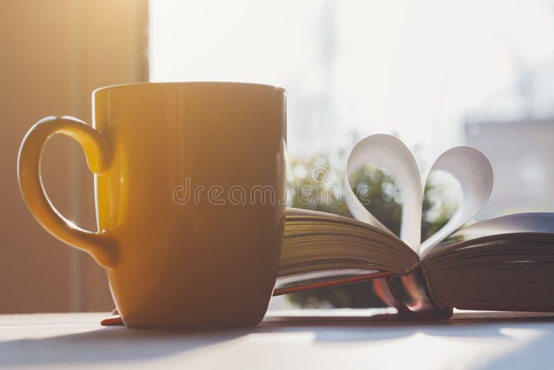 Het open die boek met pagina's als hart gestalte worden gegeven en de gele koffie vormen op houten lijst tot een kom stock foto