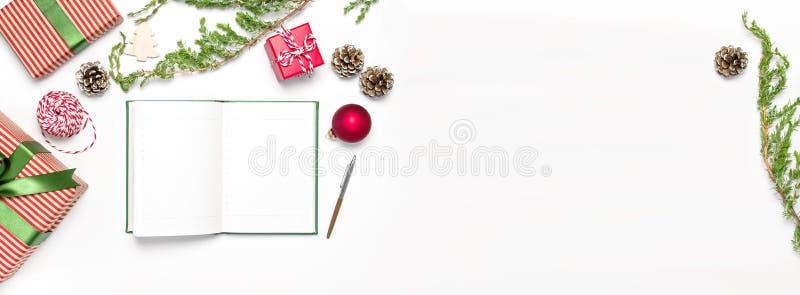 Het open notitieboekje met blanco pagina's, giftvakjes, spartakken op witte vlakte als achtergrond legt hoogste mening Kerstmis d stock foto