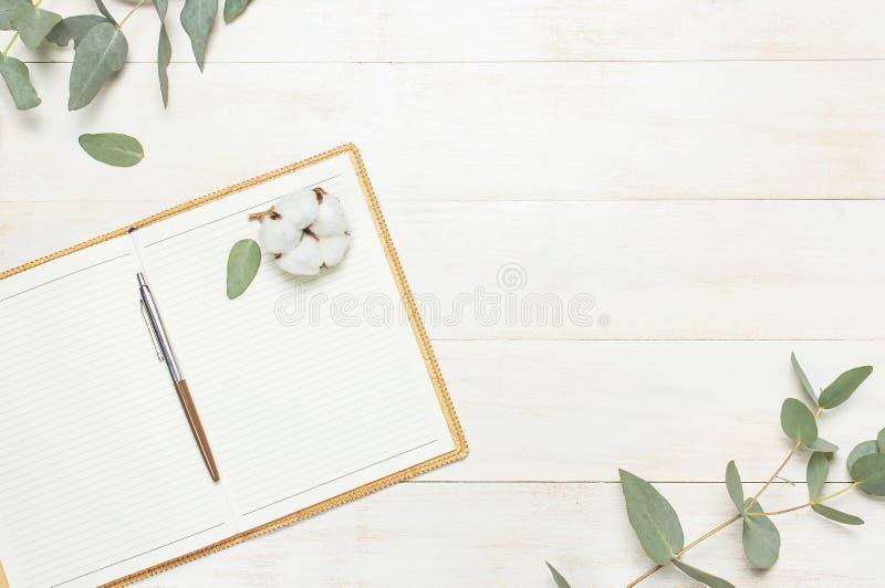 Het open notitieboekje met blanco pagina's, pen, eucalyptustakje en katoenen bloemen op witte houten achtergrond hoogste meningsv royalty-vrije stock foto