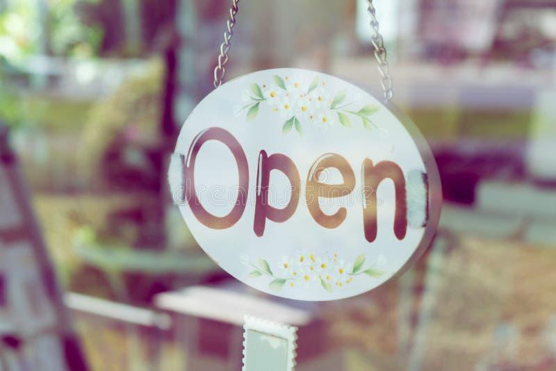 Het open teken brede hangen op deurspiegel in koffiewinkel stock afbeelding