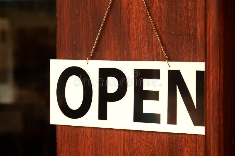 Het open teken brede hangen op houten deur in straatkoffie stock afbeelding