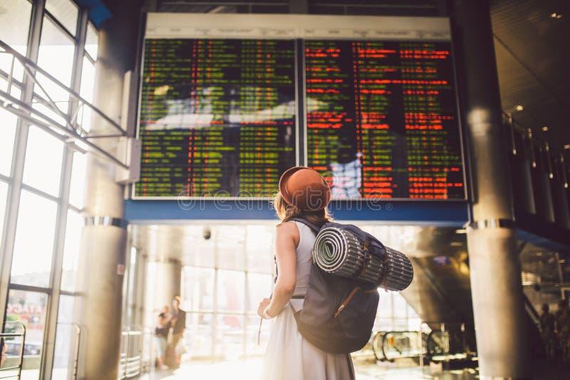 Het openbare vervoer van de themareis jonge vrouw met in kleding en hoed achter rugzak achteruitgaan en het kamperen materiaal di stock afbeelding