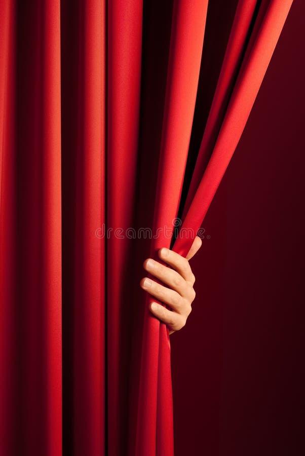 het openen van het rode gordijn royalty-vrije stock afbeeldingen