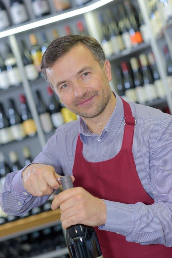 Het openen van wijnfles met kurketrekker in bar royalty-vrije stock afbeelding