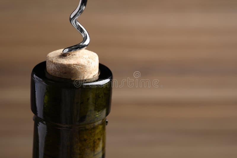 Het openen van wijnfles met kurketrekker op kleurenachtergrond, close-up stock foto