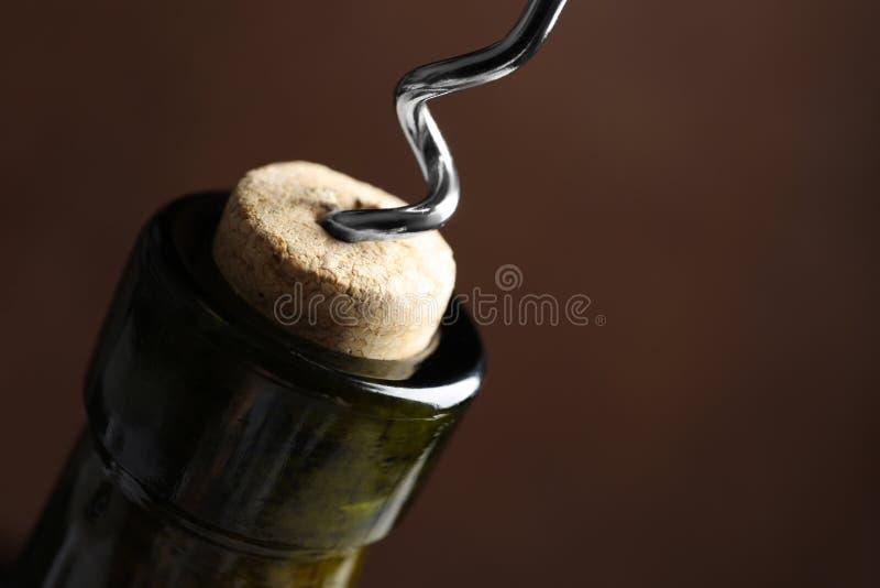 Het openen van wijnfles met kurketrekker op kleurenachtergrond, close-up stock fotografie