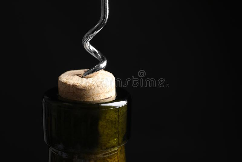 Het openen van wijnfles met kurketrekker op zwarte achtergrond, close-up royalty-vrije stock afbeeldingen