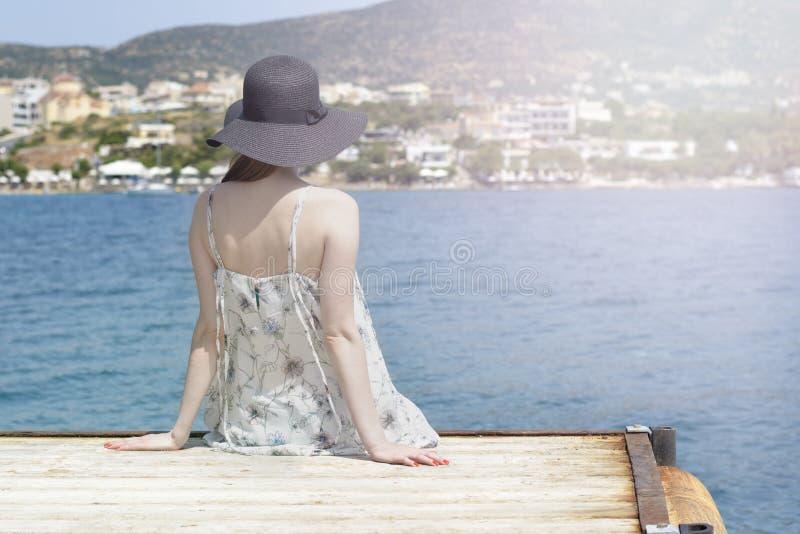 Het openlucht de zomerportret van jonge mooie vrouw die het overzees in de haven van Agios Nikolaos bekijken, geniet van haar vri royalty-vrije stock afbeeldingen