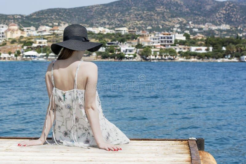 Het openlucht de zomerportret van jonge mooie vrouw die het overzees in de haven van Agios Nikolaos bekijken, geniet van haar vri royalty-vrije stock foto