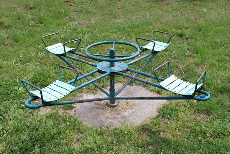 Het openlucht openbare uitstekende metaal van het speelplaatsmateriaal vrolijk-gaan-rond met geroest kader en dilapidated zetels royalty-vrije stock afbeelding