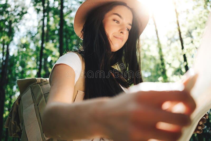 Het openluchtmeisje van de portret jonge moedige reiziger met reizende de plaatskaart van de rugzakgreep ter beschikking royalty-vrije stock afbeelding