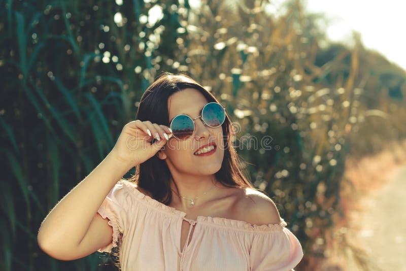 Het openluchtportret van een mooie vrouw die en zonnebril openlucht in glimlachen dragen glanst dag royalty-vrije stock afbeeldingen