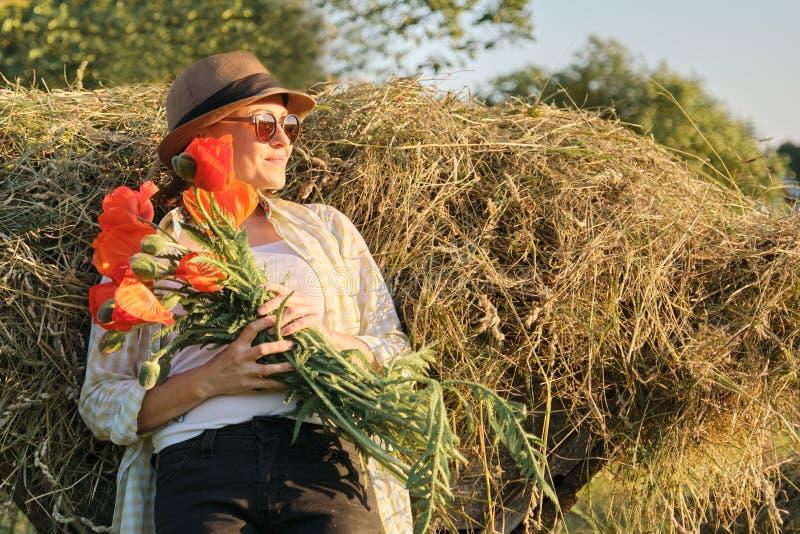 Het openluchtportret van gelukkige rijpe vrouw met een boeket van papaversrood bloeit stock fotografie