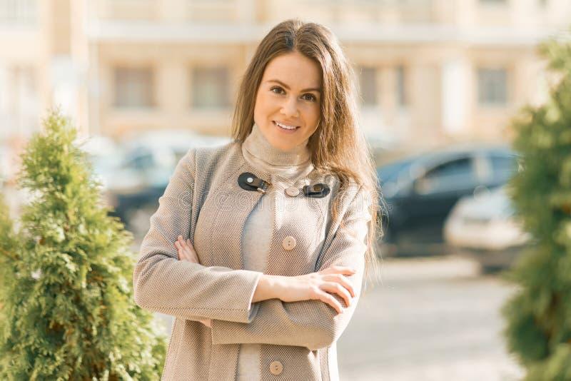 Het openluchtportret van glimlachende jonge vrouw met wapens kruiste, de achtergrond van de stadsstraat, de herfst zonnige dag stock foto's