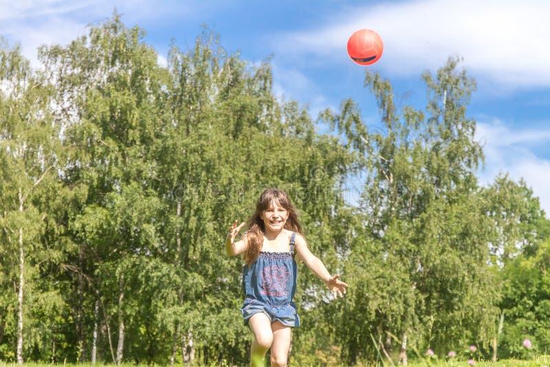 Het openluchtportret van het jonge gelukkige meisje spelen zal bal stock afbeeldingen
