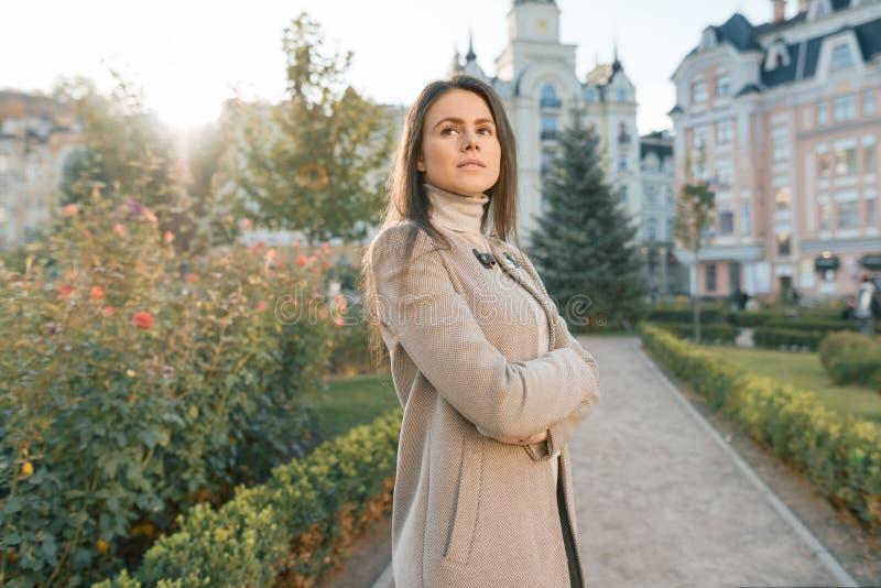 Het openluchtportret van jonge ernstige zekere vrouw met wapens kruiste, de achtergrond van de stadsstraat, de herfst zonnige dag stock afbeeldingen